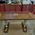 Finished teak boat table with numerous precision carved teak inalys