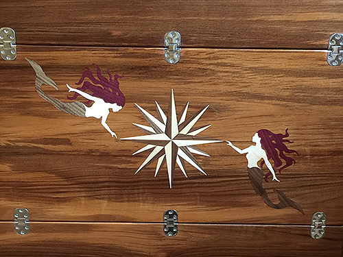 Teak inlays of compass rose and mermaids for boat table