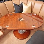 Teak boat table with inlaid design and leaves unfolded
