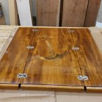 Carved teak inlay of anchor and rope for boat table