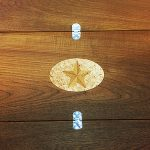 Inlaid teak star for boat dining table